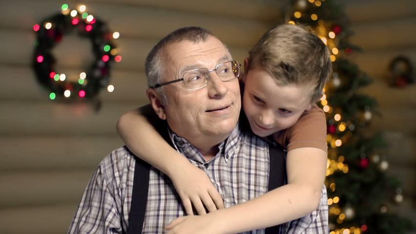 Waist up shot of grandson hugging his grandfather joyously