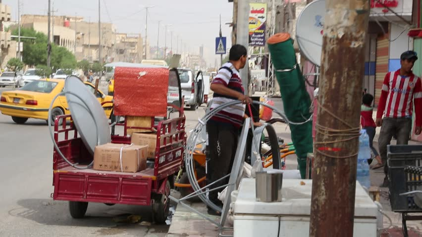 Baghdad, Iraq, October 2014: Iraqi Men Unload a Handcart Outside of a Hardware Store located in Baghdad, Iraq, October 2014.