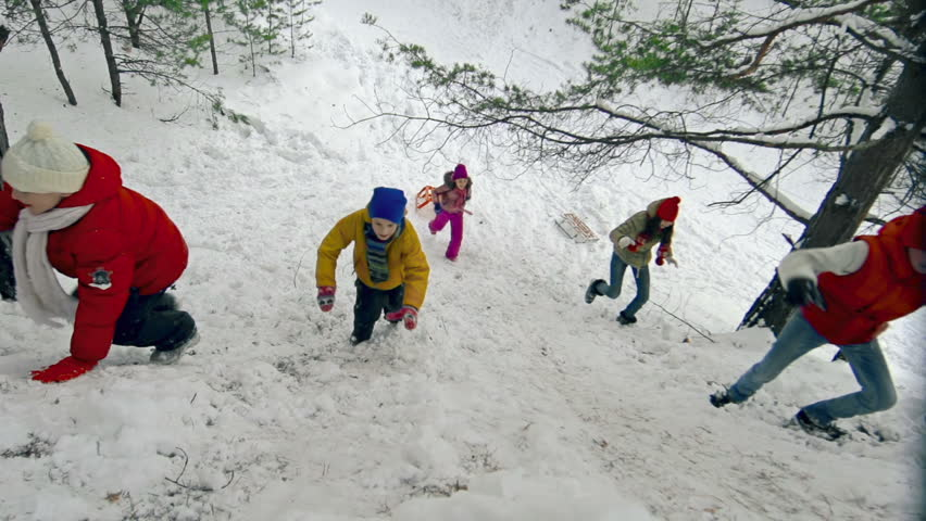 Right from above view of five jolly children climbing up the snowy hill