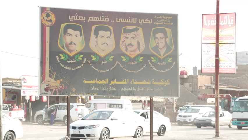 Basra, Iraq, October 2014: Pan Shot From Signboard of Posted Iraqi Faces to Pedestrians and Vehicles on the Street in Basra, Iraq, October 2014.