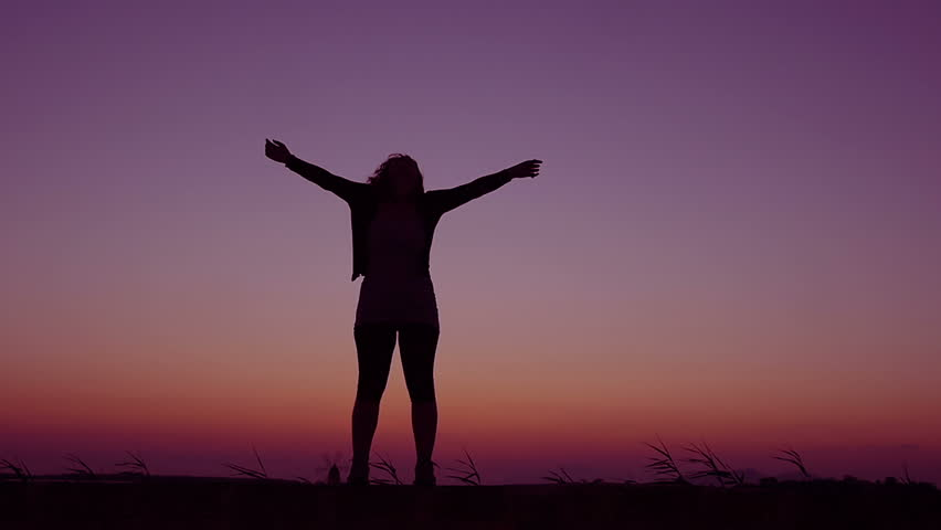 woman contemplates the sky at the sunset and opens her arms: freedom, well-being - HD stock video clip
