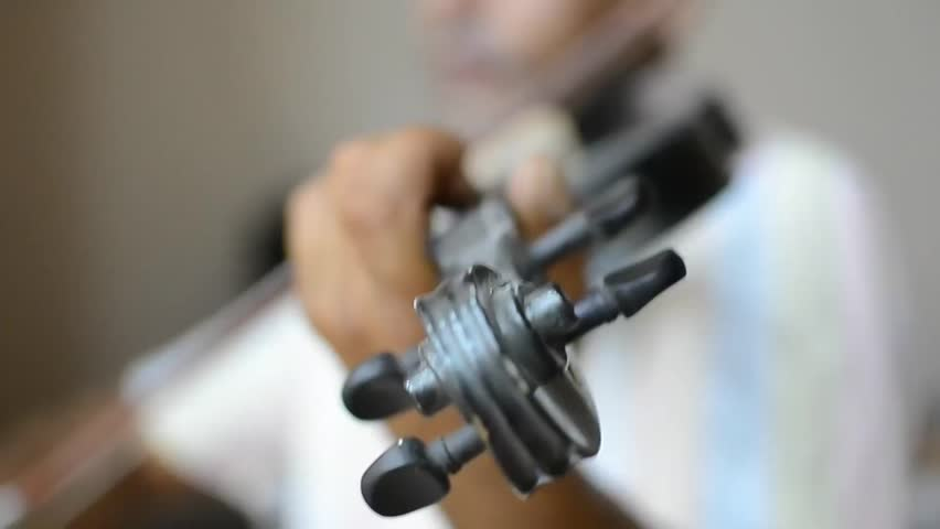 The man playing the violin. The violin is a string instrument, usually with four strings tuned in perfect fifths. It is the smallest, highest-pitched member of the violin family of string instruments, - HD stock footage clip