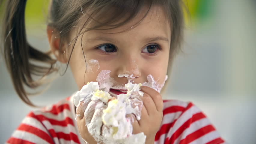 Close up of adorable little girl devouring cake with her hands - HD stock video clip