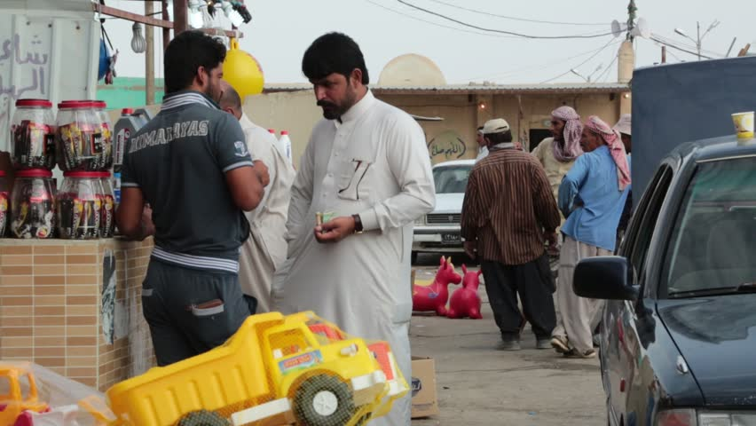 Basra, Iraq, October 2014: Two Iraqi men in traditional and non-traditional clothing have a discussion on the streets of Basra, Iraq, 2014.