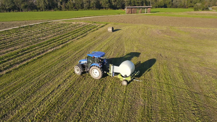 Aerial - Tractor wrapping a bale of hay in plastic protection and releasing it in a field - HD stock footage clip