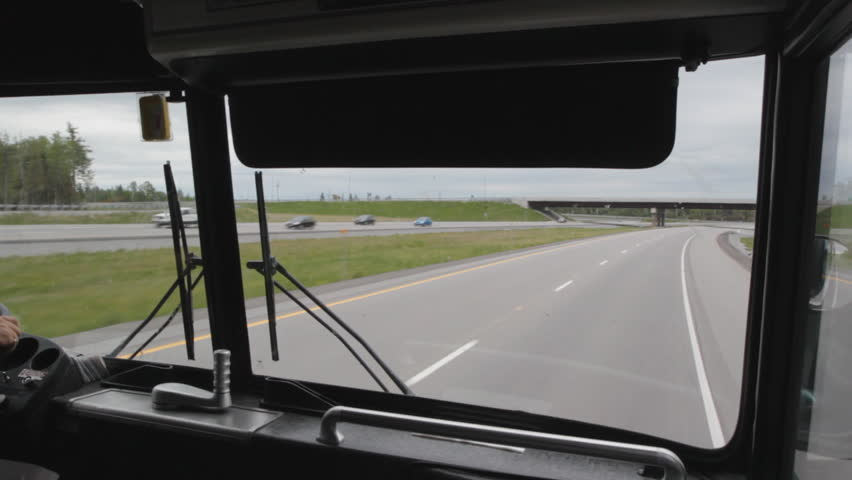 Travel by bus.  Riding at the front of a greyhound bus on Hwy 401, Ontario, Canada. Bus goes under bridge.  - HD stock footage clip