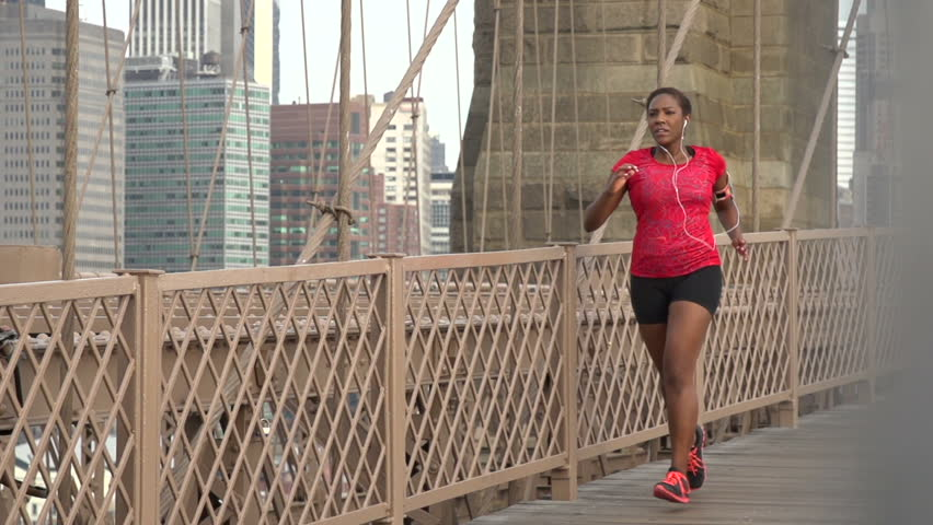 A female African American jogger on Brooklyn Bridge, New York, with Manhattan behind - slow motion | Shutterstock HD Video #7972996