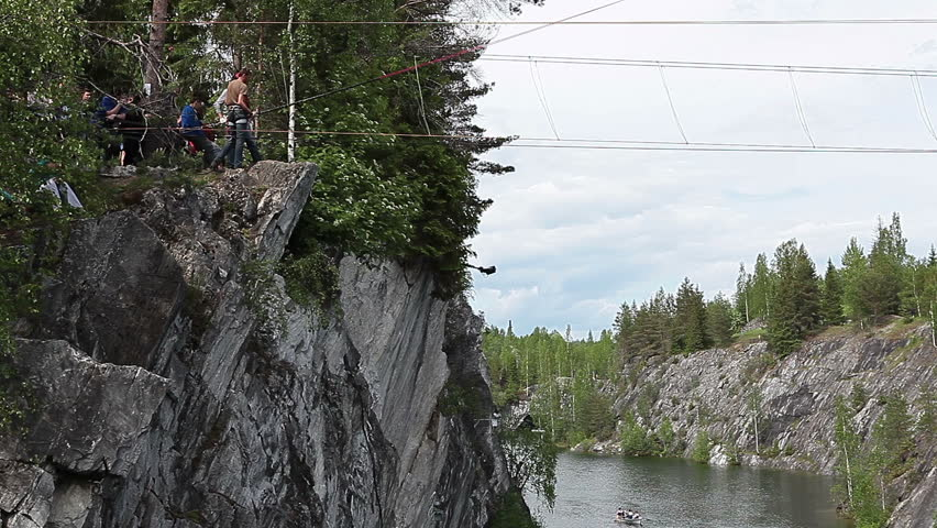 RUSKEALA, KARELIA, RUSSIA - CiRCA JUNE, 2012: Man is ready to jump with bungee rope from rock. The Ruskeala Park with green marble indundated quarry is touristic famous place in Karelia - HD stock video clip