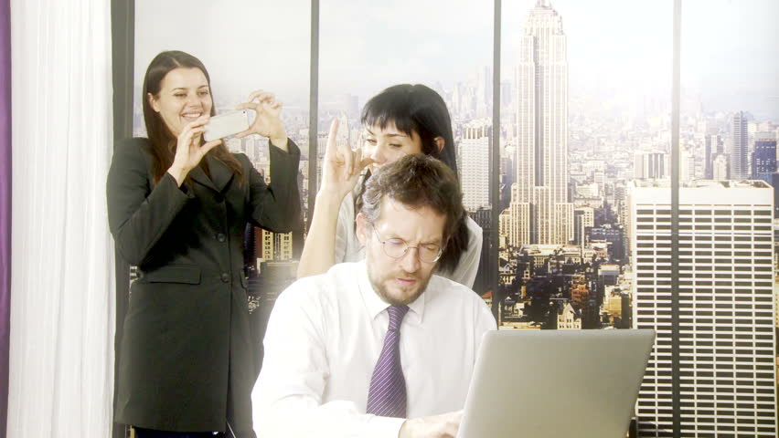 Two women in office teasing man working with computer | Shutterstock HD Video #7988944