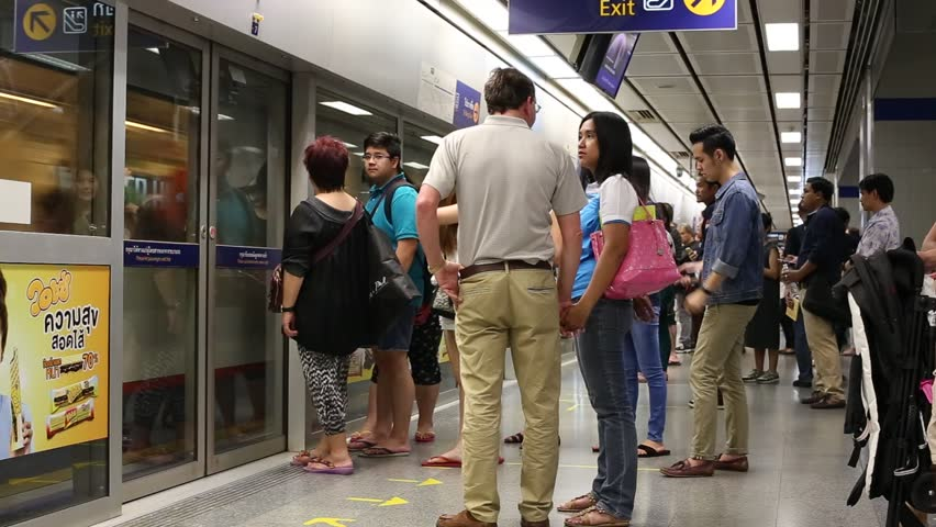 BANGKOK,THAILAND - NOVEMBER 18, 2014 : Unidentified people disembark an MRT train at an underground station. The MRT serves 240,000 passengers daily with 20 km of city centre track. - HD stock video clip