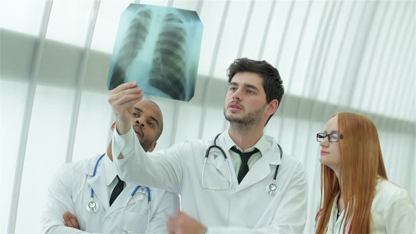 Healthy lungs and the dangers of smoking. Three confident doctor examining x-ray snapshot of lungs