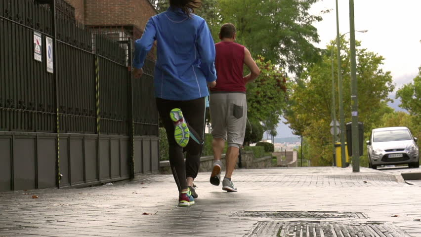 People jogging on the pavement, slow motion shot, steadycam shot  | Shutterstock HD Video #8018077