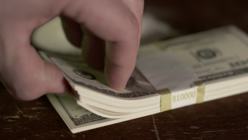 Drugs and Money - Substance abuse with drugs and a stack of hundred dollar bills sitting on a table