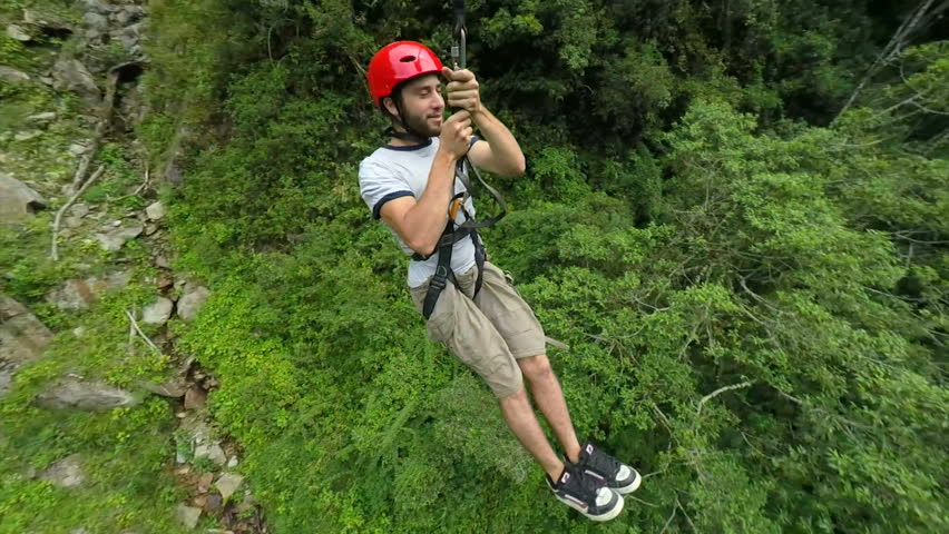 Young man sliding on zip line , camera rotates 360 degrees and track the subject , slow motion 120fps | Shutterstock HD Video #8031640