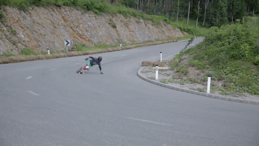 OSILNICA, SLOVENIA - AUGUST 2014: Longboard skate left turn. Skateboarding left turn on a slippery mountain road during extreme adrenalin competition sport event - HD stock footage clip