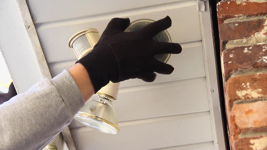 Light Bulb Of An Outdoor Motion Security Light Is Removed And Replaced By Male Hand Wearing Black Gloves And Then Adjusts A Switch - HD stock footage clip