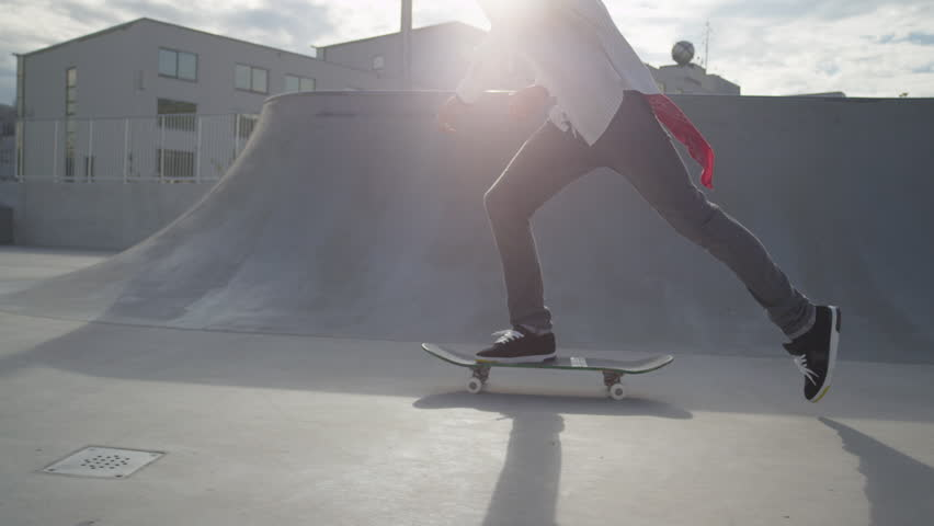 SLOW MOTION: Skateboarder jumps on his skate and starts cruising