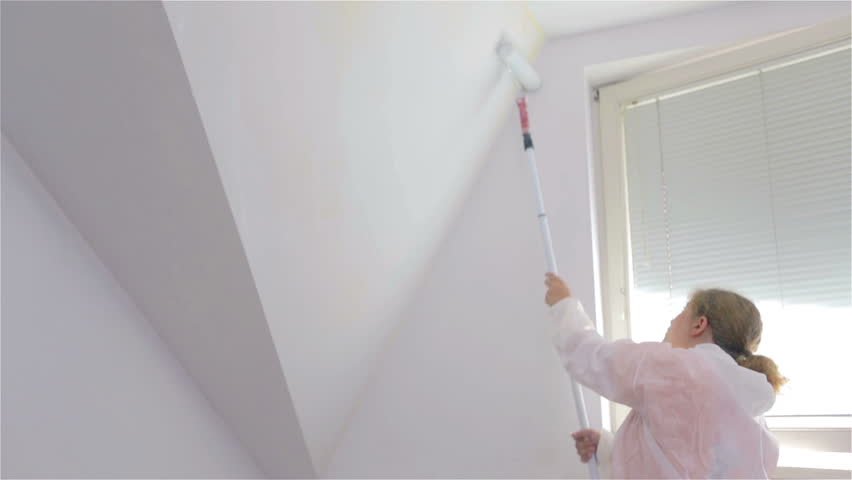 Woman paint sloped wall with roller on pole. Low angle shot of female in protective suit painting room with roller on long pole. | Shutterstock HD Video #8070394