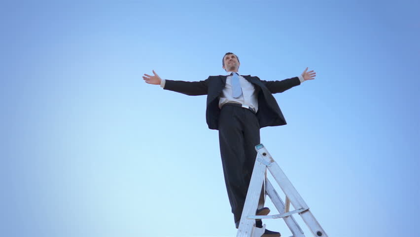 Businessman in a suit and tie standing on a ladder against a clear blue sky with his arms spread wide open. #8079646