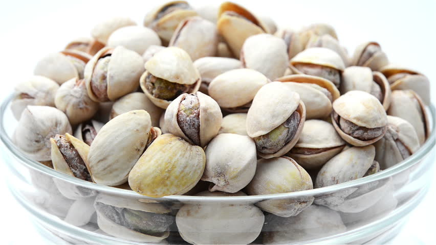 roasted salted appetizing pistachios in glass bowl rotating