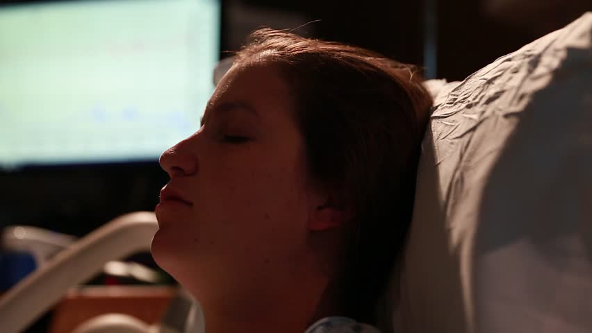 A pregnant woman in labor at the hospital on a bed with nurses in the room | Shutterstock HD Video #8113315