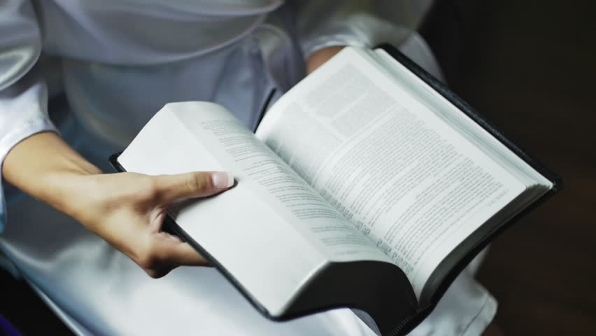 a slow motion shot of a woman flipping the pages of a bible - HD stock video clip