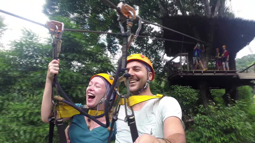 Couple on ZIP-LINE. Couple enjoying on zipline attraction.