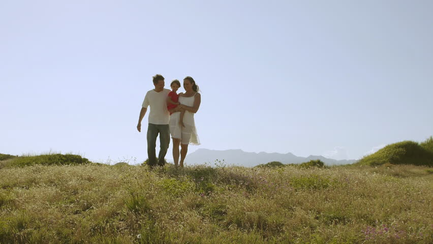 Family Walking Through Meadow To Camera. - HD stock video clip