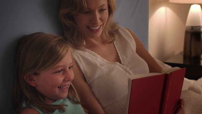 Mother And Daughter Reading In Bed. - HD stock video clip