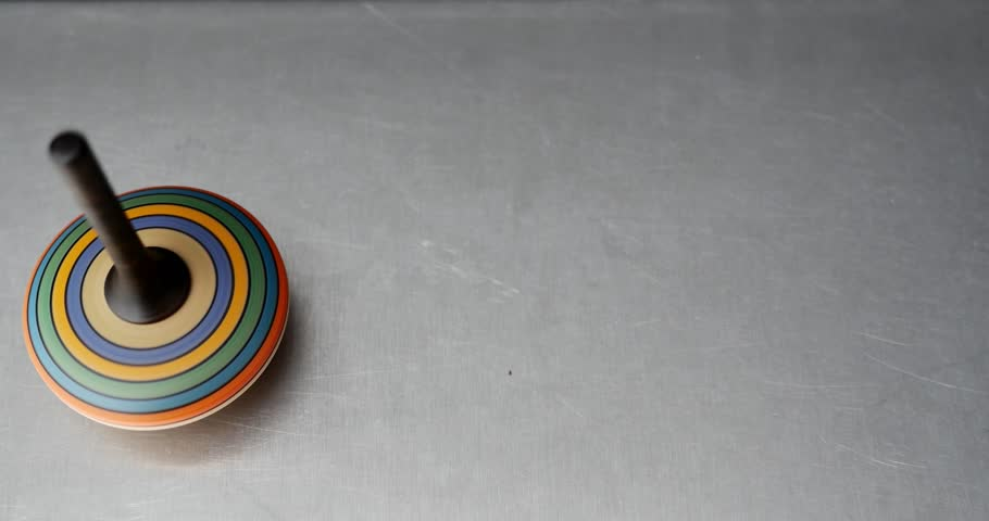 High shot of a colorful spinning top spinning on a metal table/Whos gonna spin longer - 4K stock footage clip
