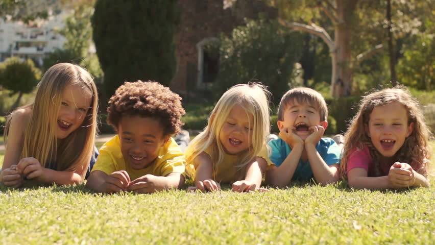 Five Children Lying On Grass In Park Looking At Camera. - HD stock video clip