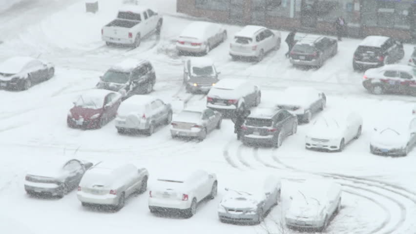 Vehicles covered in snow in parking lot during a snowstorm.