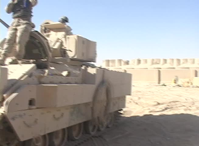 Iraq, Circa 2009: US Army Soldier adjusts his helmet strap while standing on a  Bradley Fighting Vehicle in preparation for a mission in Iraq, Circa 2009.