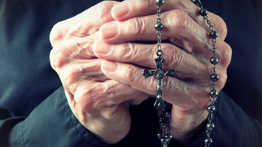 Old lady hands holding a Catholic rosary or cucifix and praying to God in Heaven. Daily traditional Catholic devotional of an old lady or woman.