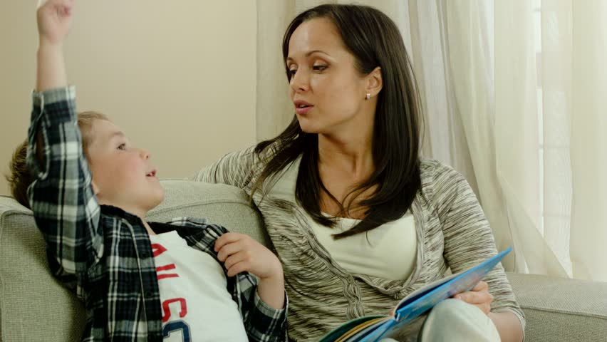 Mother with her son on a sofa in home interior reading book