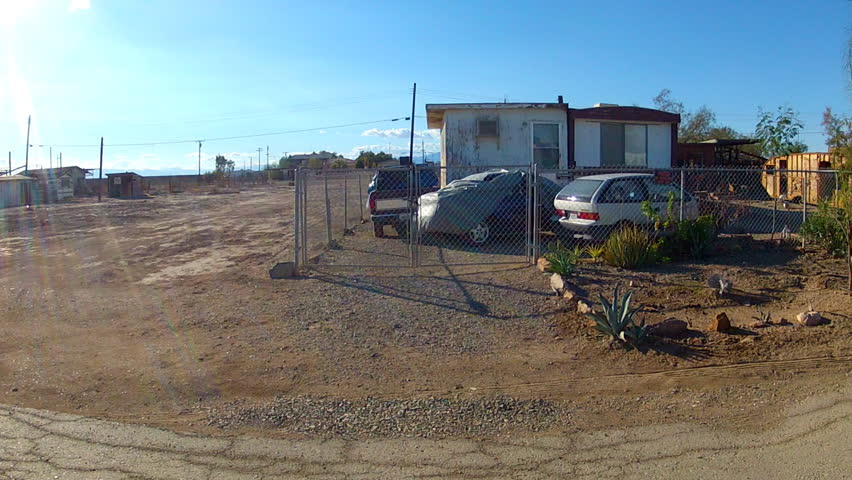 BOMBAY BEACH, CA: December 6, 2014- POV vehicle driving shot of trailer park living circa 2014 in Bombay Beach.  Desert community is comprised of low cost housing including trailers and motor homes.