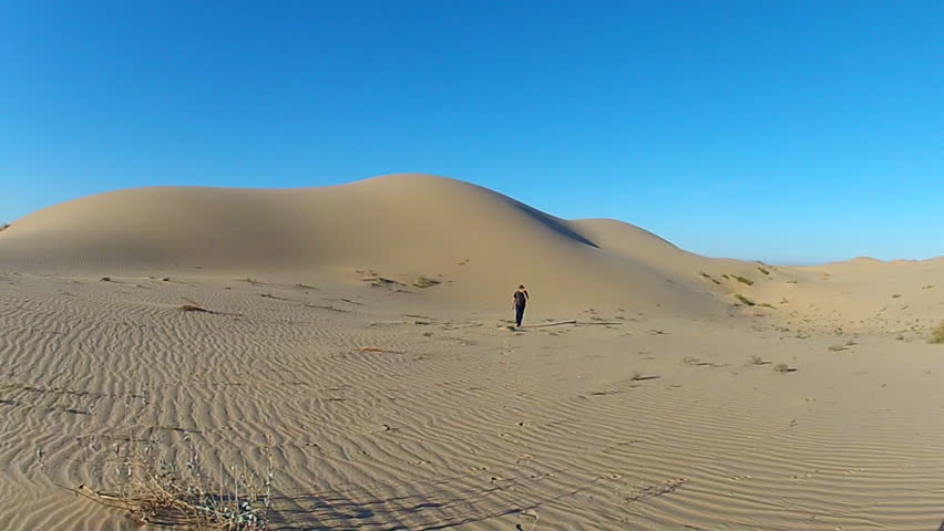 Shot of a man as he walks toward camera in a sandy desert. A Glamis California hiker returns from a walk after exploring a large sand dune in the distance. - HD stock footage clip