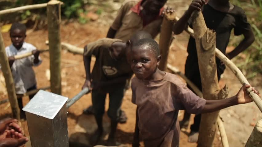 LUWERO, UGANDA - SEPTEMBER 2013: Happy African kids celebrate the installation of a new water well in their village