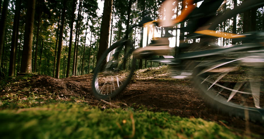 Mountain Biker downhill with MTB in 4k slow motion On Forest Trail kicking up dirt