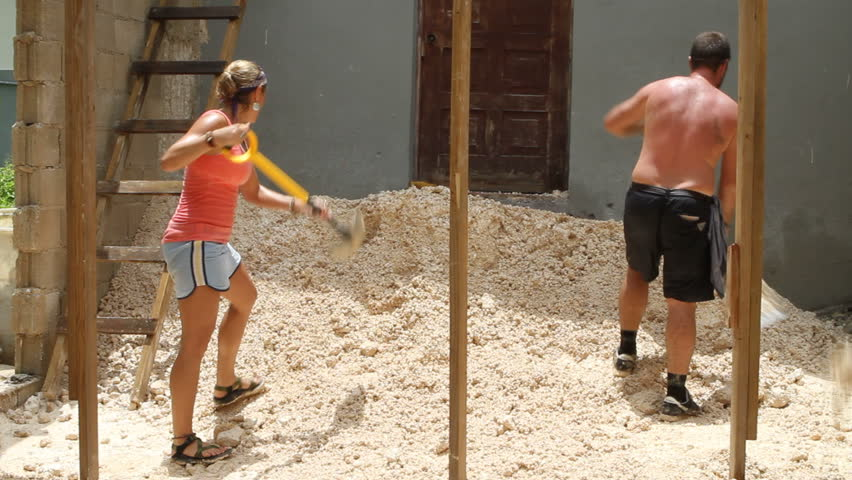 Two young adult missionaries use shovels to spread fill dirt around the basement of a church they are helping to construct. - HD stock video clip