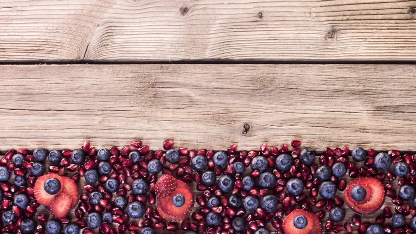 Cocktail of blueberry pomegranate and strawberries on a wooden table | Shutterstock HD Video #8402521