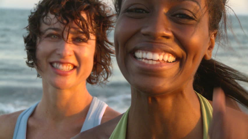 Portrait of two young women at beach during sunset - HD stock video clip