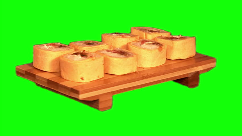 "Sushi (rice, salmon, cucumber, Japanese seasoning, spring onion, cheese ""Philadelphia"", cheese flat cake) on the wooden stand rotating on green screen, loop 
