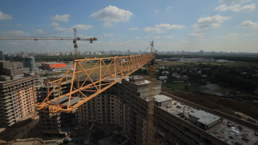 Industry and development. Construction of high-rise buildings.Aerial shots. Camera flies past a construction crane boom and opens overall plan construction site