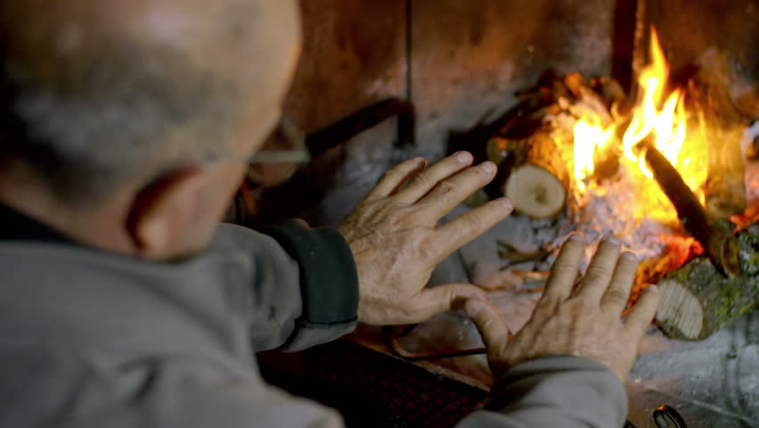 warm up the hands to the fire near the fireplace: wood, flame, tradition, winter - 4K stock footage clip