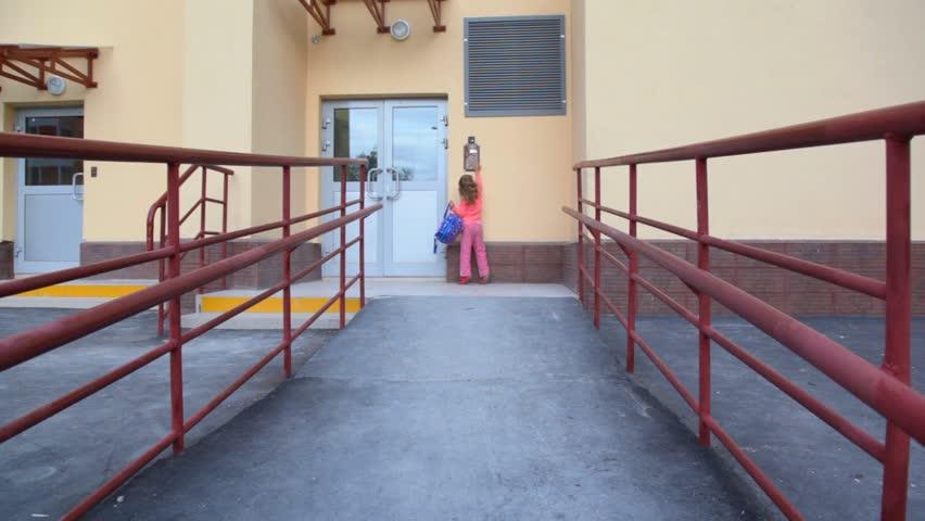 little girl with rucksack using door intercommunication system