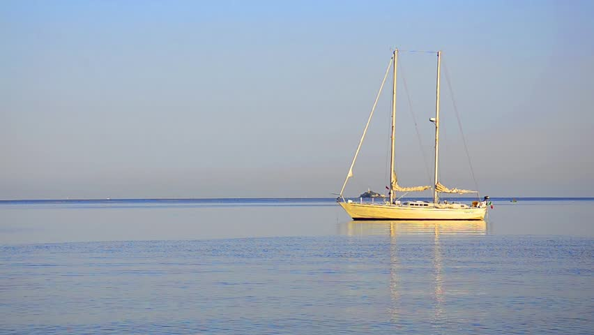 A sailboat on the horizon in the beautiful Caribbean ocean sunrise LOOP - HD stock video clip