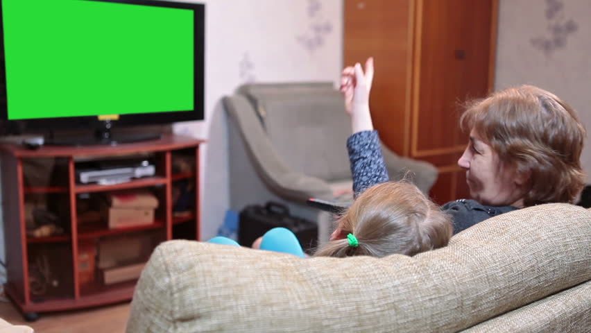 Mother And Her Daughter Watching Green Screen Tv In Living ...