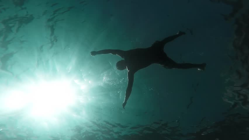 Silhouette Man Drowning Sinking Body In Deep Water Slow Motion Underwater Shot Ocean Murder Danger Lost At Sea Drown Death Lifeless Swimmer Sun Rays Waves Ripples Mortality Concept Gopro HD