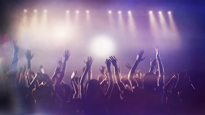 Footage of a crowd partying, dancing slow motion at a concert